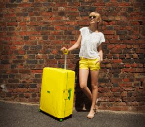 chica con una maleta grande amarilla