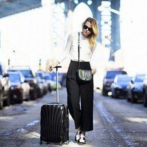 mujer con una maleta rígida pequeña