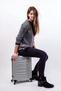 chica con una maleta gris