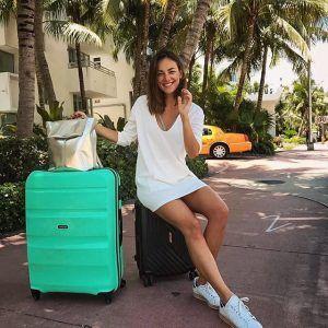 chica con dos maletas American Tourister
