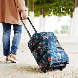 chica llevando una maleta de mano blanda