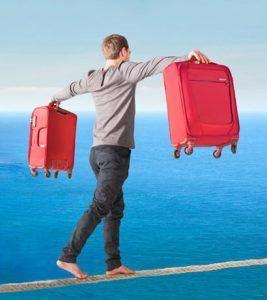 hombre sujetando dos maletas