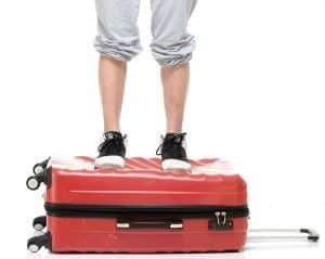 persona sobre una maleta rígida