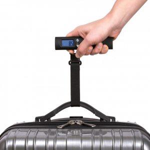 persona usando una báscula para maletas