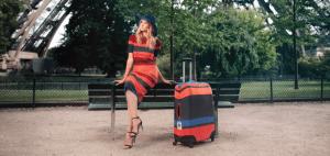 mujer con una maleta con funda para maleta